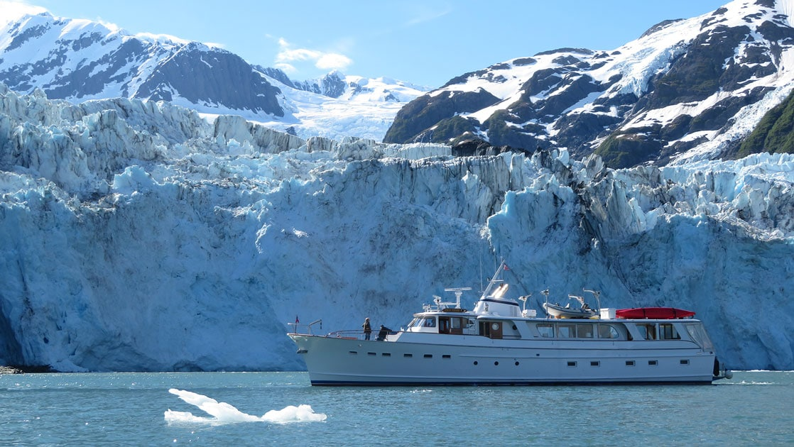 Small white yacht idles in front of a large blue & white glacier on a sunny day in Alaska, with iceberg floating beside the ship.