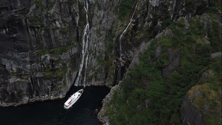 Aerial view of Sea Star small white yacht idling beside tall rock walls with waterfalls during a Kenai Fjords NP cruise.