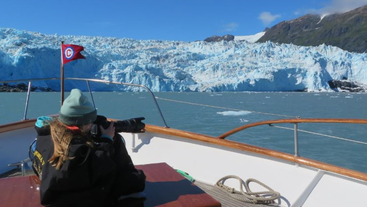 Alaska traveler sits near bow of a small yacht with camera out, photographing an icy blue glacier on a sunny, clear day.