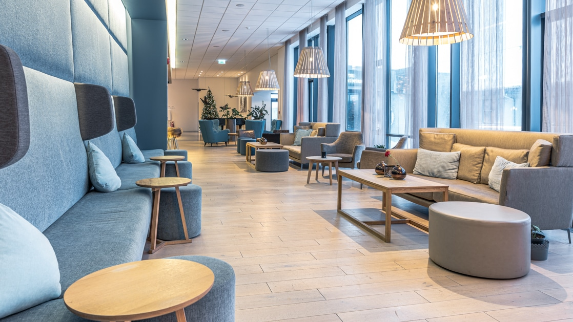 Lobby of Hotel Vik i Myrdal, with wall of teal couch, wooden coffee tables, wood flooring, gray couches, hanging lamps & floor-to-ceiling windows.
