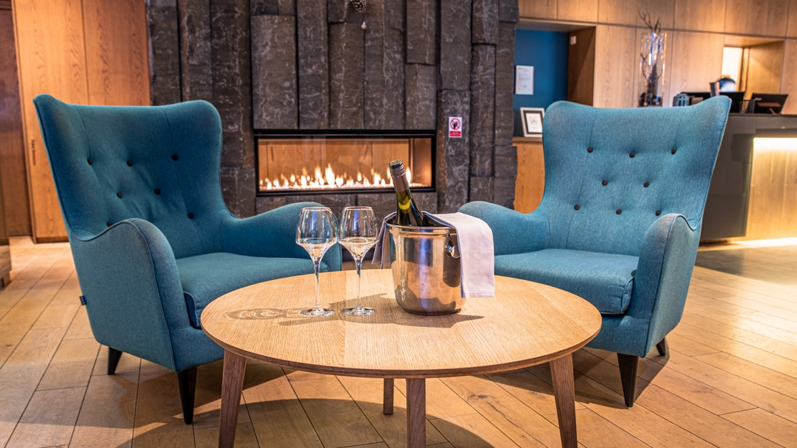 Reception lobby at Hotel Vik i Myrdal, with gas fireplace, wood flooring, 2 teal wingback chairs & wooden coffee table set for champagne service.