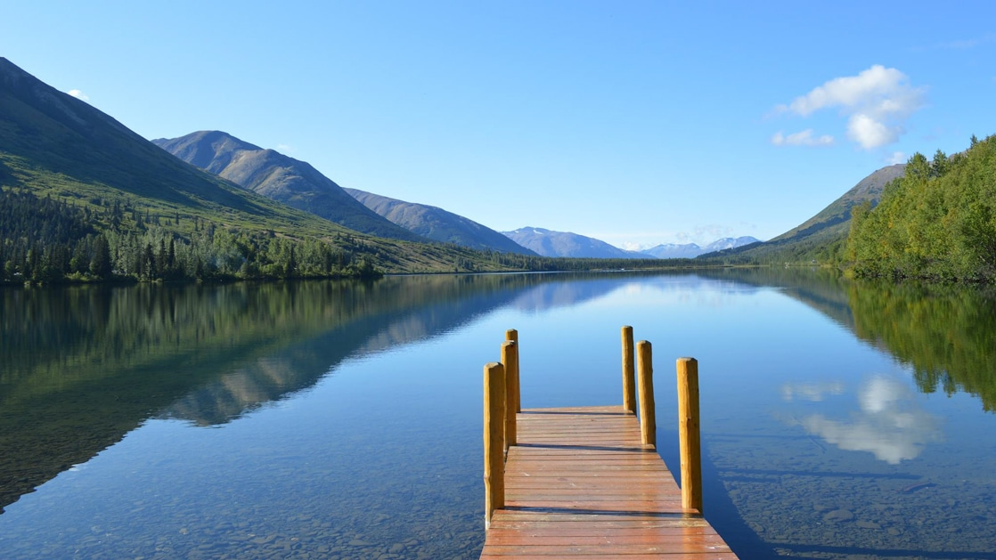 Empty wooden dock leads onto glassy Summit Lake surrounded by green mountains on a clear, sunny day in Moose Pass, Kenai, Alaska.