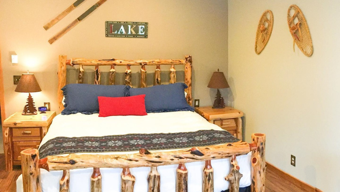 Modern & rustic log bed covered in quality linens with bedside tables & lamps in a modern cabin with snowshoes & old skis on the wall.