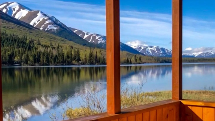 View from a lakefront cabin wooden porch at the Summit Lake Lodge, on a sunny day with glassy water reflecting the hills & mountains.