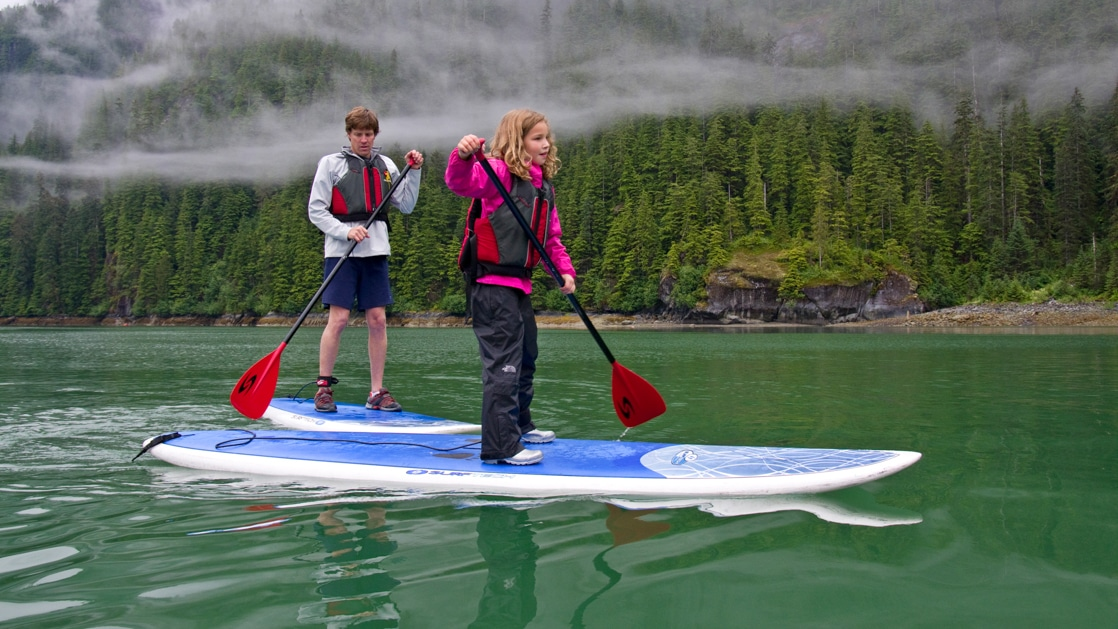 Red-headed boy & younger blonde girl each paddle a stand-up paddleboard in calm, green-tinted water during an Alaska family cruise.