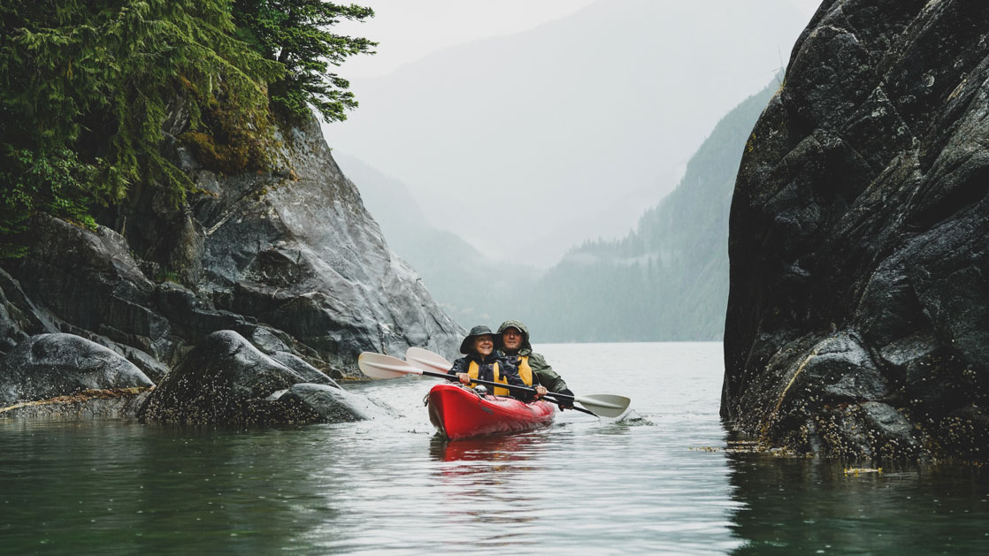 Tandem kayakers in a red boat paddle calm water between large dark boulders on a misty day during the Wild & Wooly Alaska Cruise.