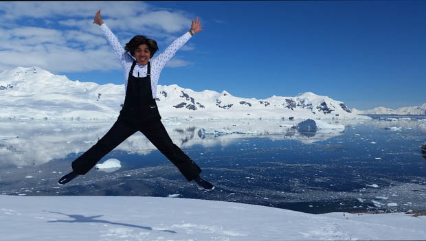 A woman in black ski overalls jumps in joy on Antarctica having reached her 7th continent in one year.