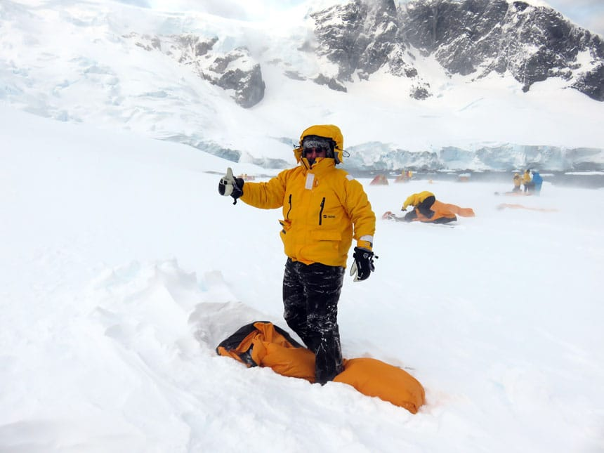 polar traveler in yellow jacket gives the thumbs up while standing over a yellow bivvy sack atop a snowfield while camping in antarctica.