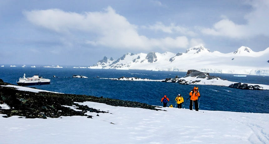 3 polar travelers in bright red, yellow & orange jackets hike up a snow field on a sunny day. An answer to why go to Antarctica.