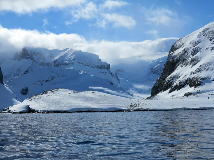 Cuverville Island covered in snow with dark cliff features & tiny specks of penguins on a sunny day with water in the foreground.