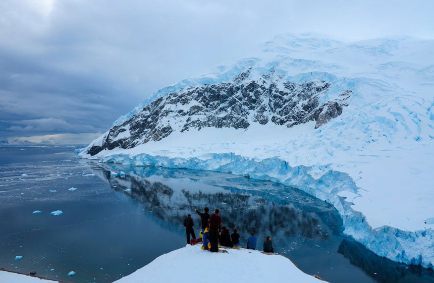 Neko Harbor, one of the places in Antarctica, with people perched atop a lookout point viewing the glassy water below on a cloudy day.