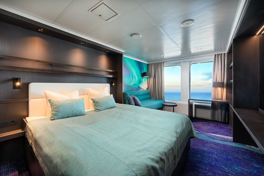 Antarctica ship cabin rendering showing two large view windows, seating area, large bed and TV.