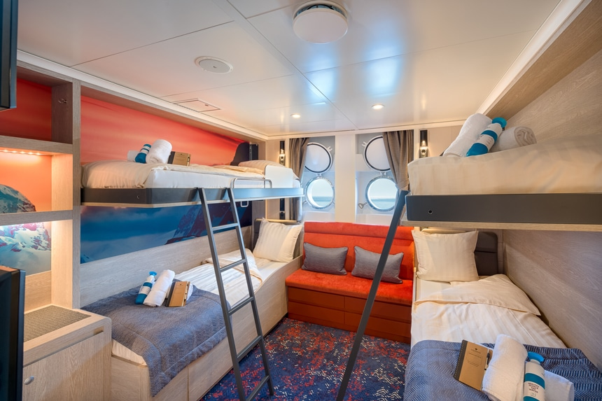 Antarctica ship cabin rendering showing 2 bunk beds with ladders with 2 porthole windows and a small seating bench between them.