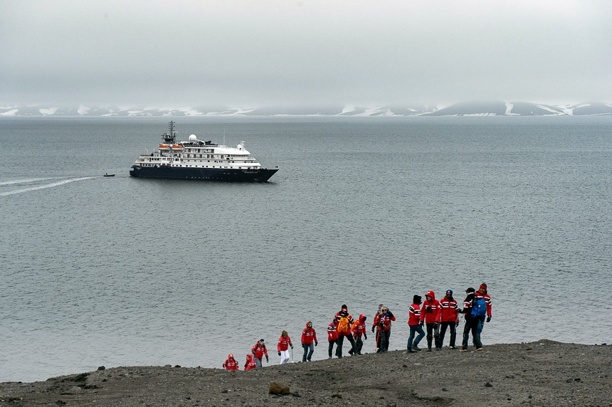 Guests wearing red parkas hike up a barren hillside in Antarctica as a blue and white ship floats in the dark ocean behind them.