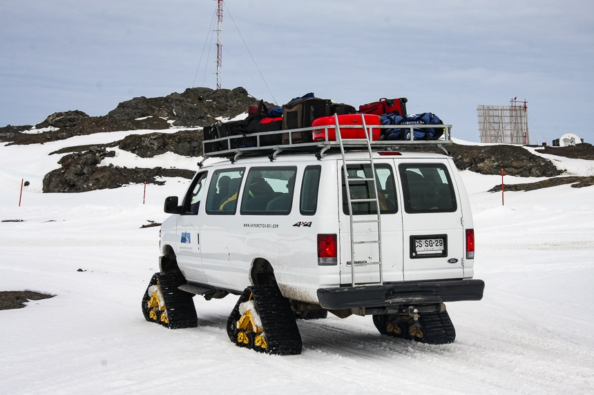A white van with tracked triangle shaped tires for snowy Antarctic driving carries guests and their luggage from the ship to the air plane for an Air Cruise itinerary