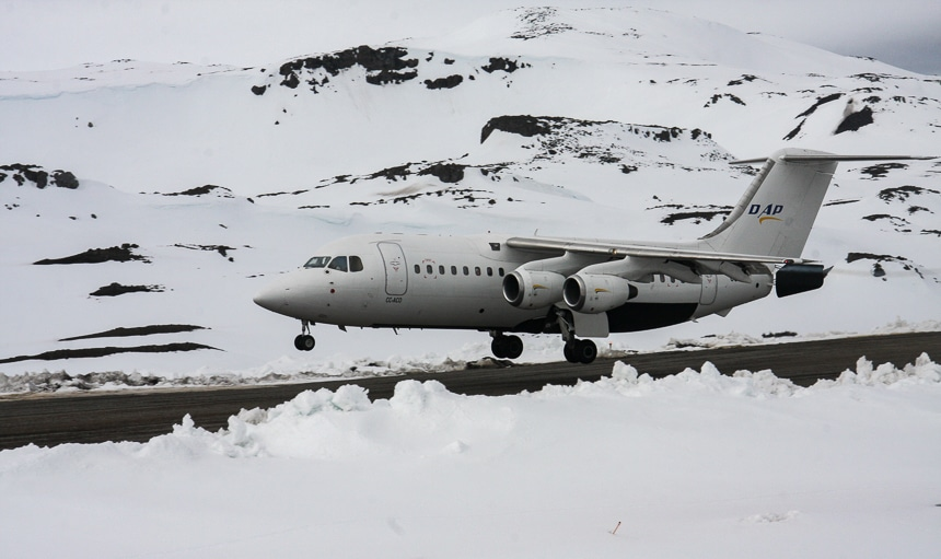 As part of an Air Cruise itinerary a white air plane lands on a grey run way in the middle of a snowy mountainous Antarctica landscape.