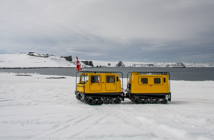 Against a grey Antarctica ocean landscape two yellow tank-like land rovers drive across the snow as part of an Air Cruise.