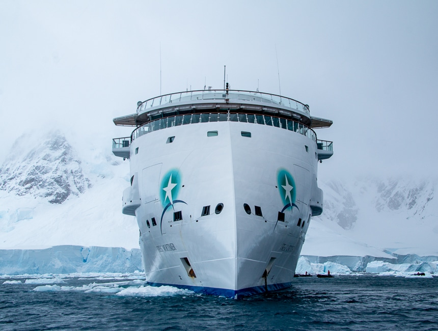 An all white futuristic and modern ship cruises the dark ocean water in front of a mist covered snowy mountain range in Antarctica.