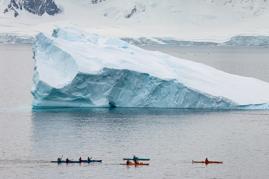 A group of kayakers are dwarfed in size as they paddle around a massive teal and white floating iceberg in Antarctica.