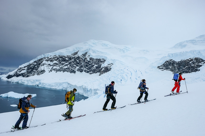 On a grey overcast day in Antarctica a group of guests ascend a snowy hillside on skis as part of an added cost activity provided by an active Antarctica cruise line.