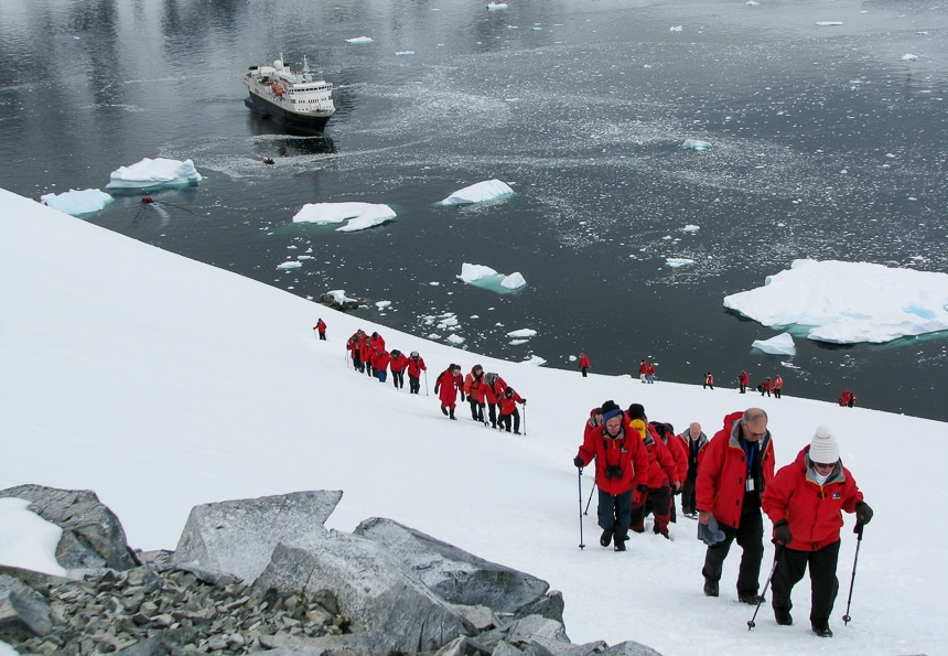 Guests wear red parkas and hike up a snowy hillside in Antarctica as part of a daily shore excursion provided by Antarctica cruise lines.