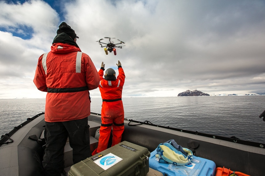 Two people wearing red parkas send a robotic drone into the air as part of scientific research program in Antarctica.