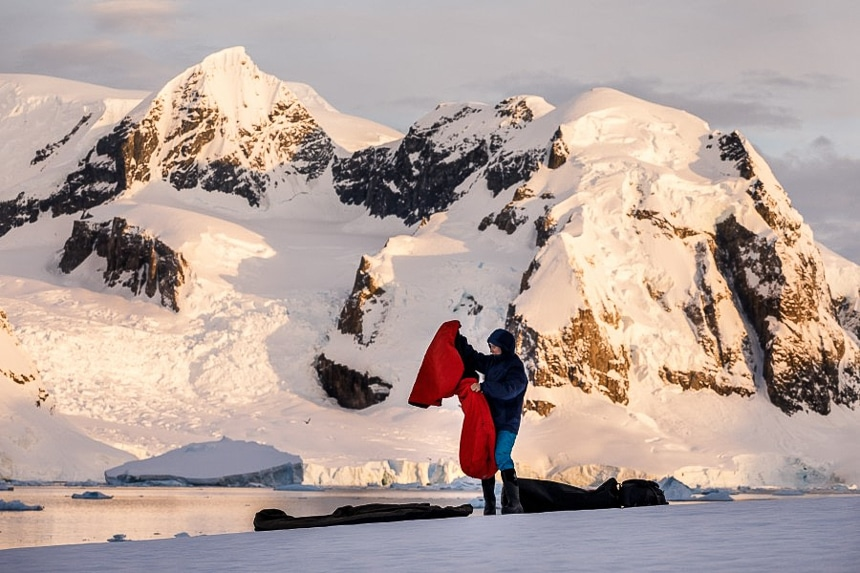 In front of a snow covered mountains cape a female guests sets up her sleeping pad and and bag as part of a polar camping activity in Antarctica.