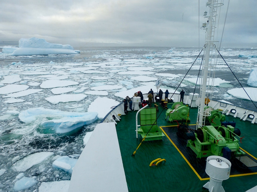 Guests gather at the bow of a ship as it breaks through a field of icebergs floating in the ocean of Antarctica.