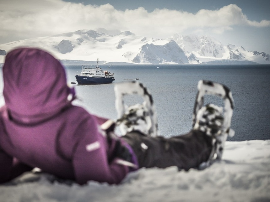 A guest wearing snowshoes lays on the snow, in the distance a blue and white ship navigates the polar ocean in front of white Antarctica mountain landscape