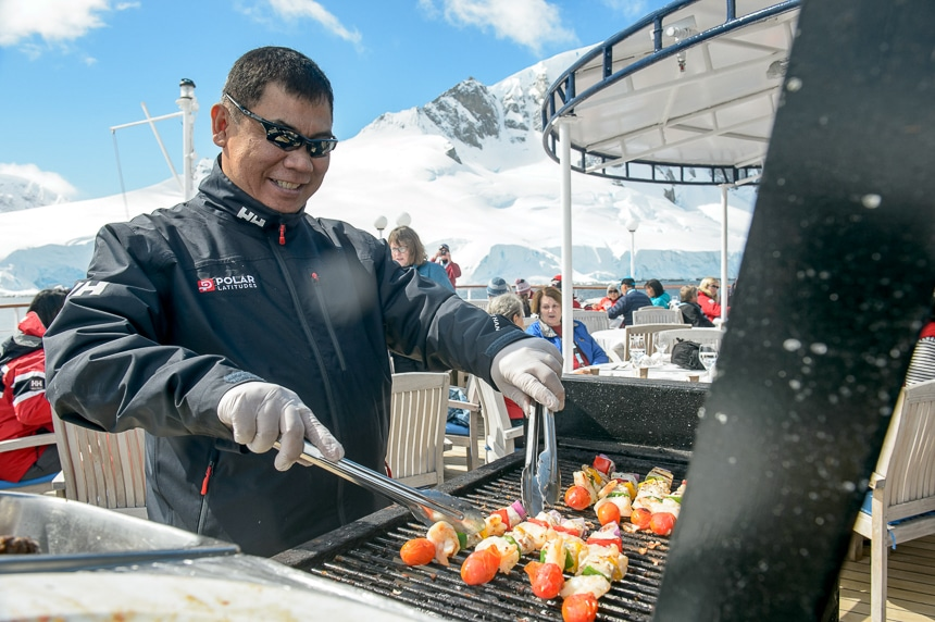 A happy crew member holds tongs and bbq's kebabs outside on a grill for a top deck outdoor dining experience in Antarctica.