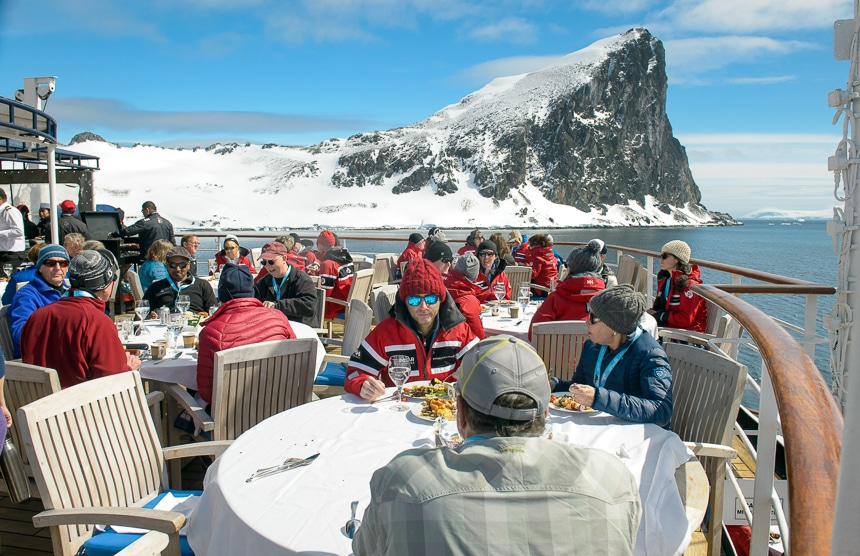 On a sunny blue sky day in Antarctica guests sit on the top deck of the ship and enjoy an outdoor BBQ lunch in front of a snow covered jagged rock formation.