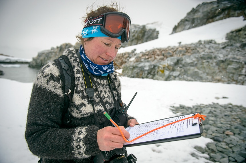 On shore in Antarctica a naturalist guide from Polar Latitudes cruise line wears snow goggles and looks down as she writes on a clipboard