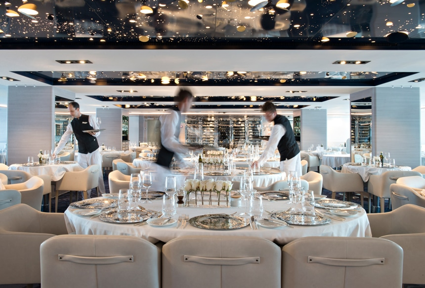 An elegant dining room aboard a luxury Antarctica cruise line filled with white tables clothes, white roses and cream leather chairs sit empty as 3 crew members set the table ware.