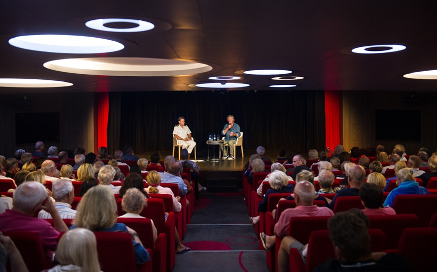 Guests sit in theatre style seating facing the stage watching two guest speakers give a lecture aboard a ponant cruise line ship.