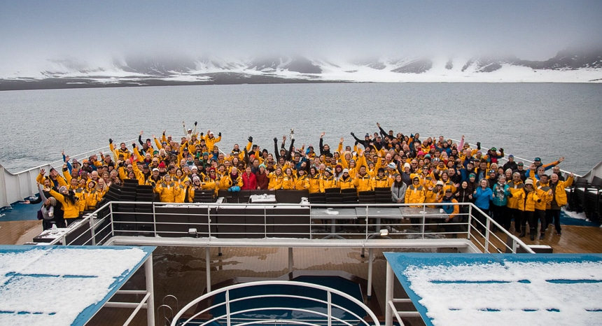 All of the guests, crew and guides from a Quark Antarctica cruise gather at the stern of the ship for a group photo in front of a snowy Antarctica mountain scape.