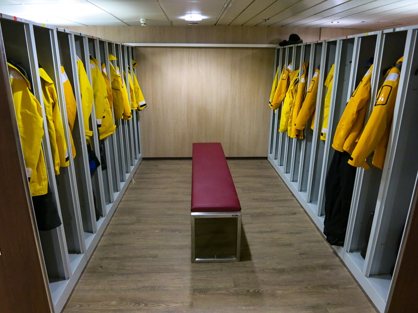 Mud room aboard Quark Antarctica cruise line ship. Yellow parkas are hung up in open long cubbies with a bench seat on the floor.