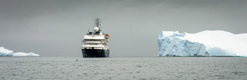 On a grey overcast day in Antarctica a white and blue ship navigates the polar ocean next to a massive white iceberg.