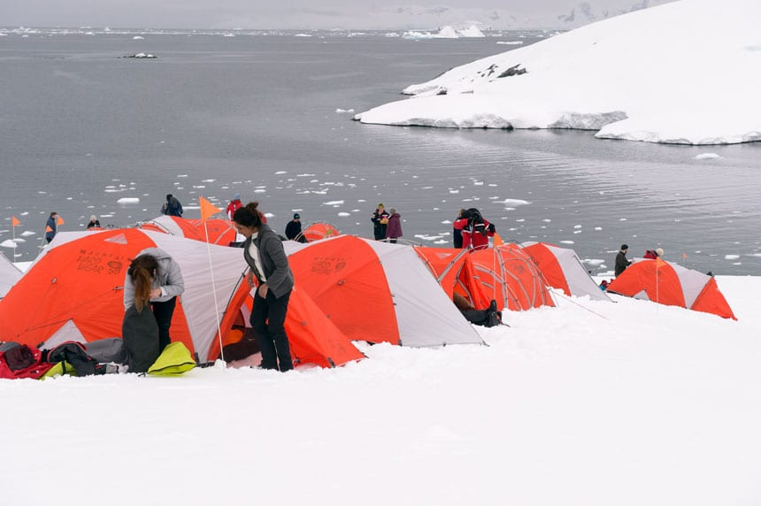 polar travelers set up orange & gray tents atop a snowfield with iceberg-filled waters behind while camping in antarctica.