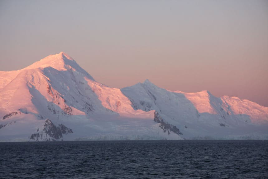Pink sunset hues on snowcapped peaks beside open ocean. An answer for should I go to Antarctica?