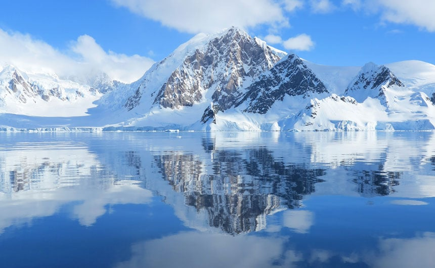Glassy water under a blue sky with some white clouds & a rocky, snow-covered peak. A reason why people want to go to Antarctica.
