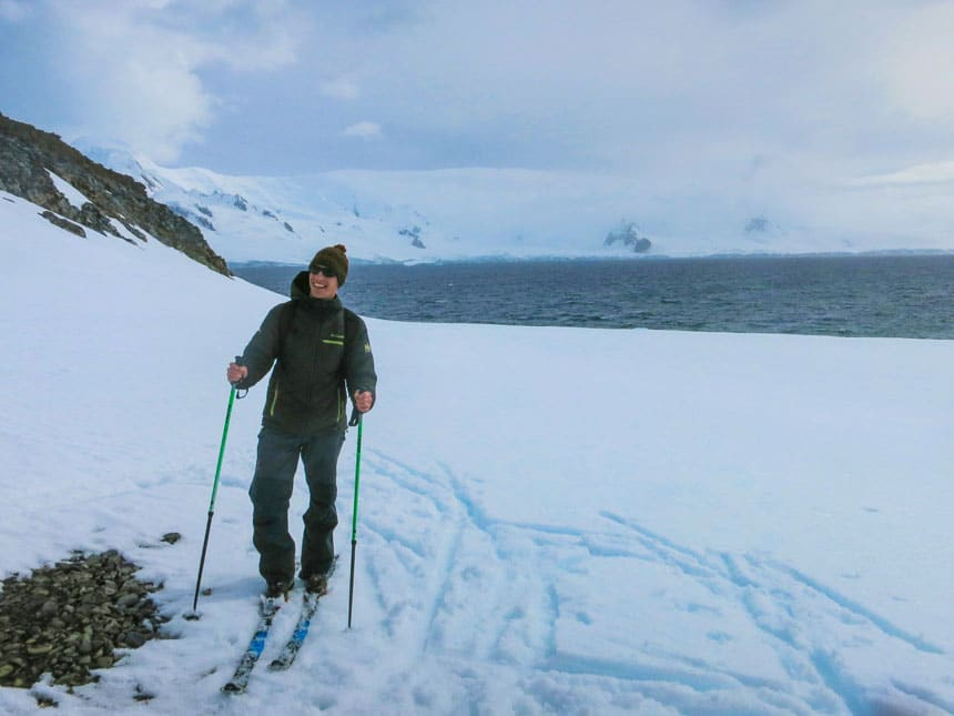 Man in dark green jacket, pants & knit hat stands on nordic skis atop snow with ocean behind, cross country skiing in antarctica.