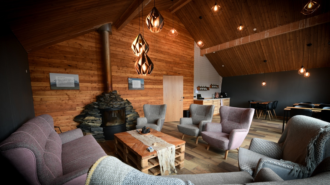 Living room with wooden walls & ceiling, pendant lamps, pink & teal couches & chairs, wood stove, recessed lights & pallet coffee table.