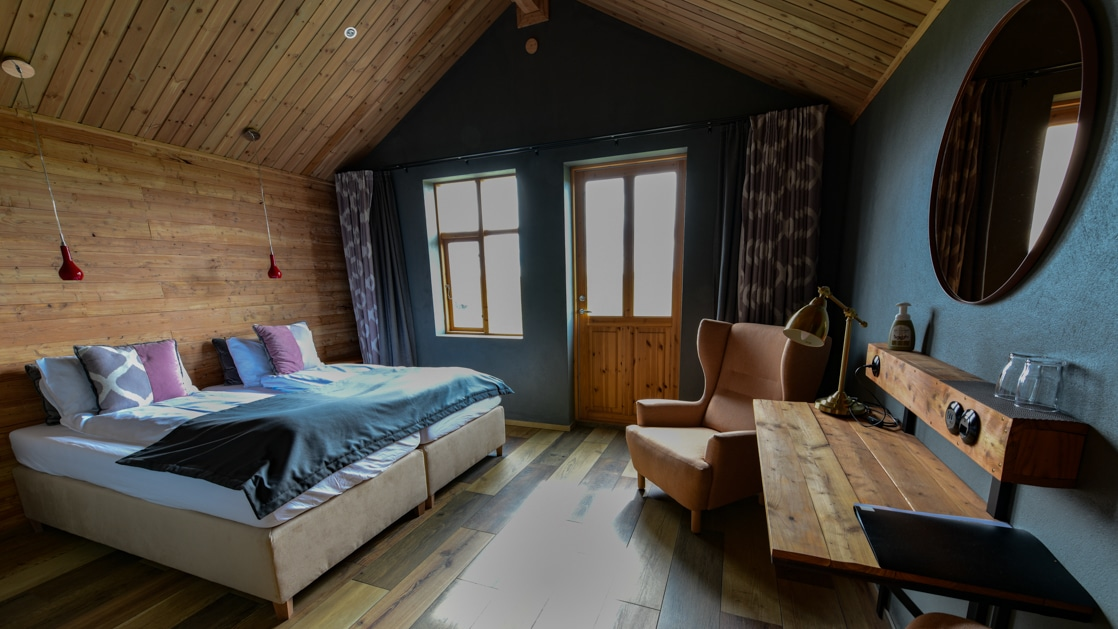 Modern guest room with double bed, wooden desk, wooden accent wall & ceiling, window, door, 3 teal walls, 2 peach armchairs & round mirror.