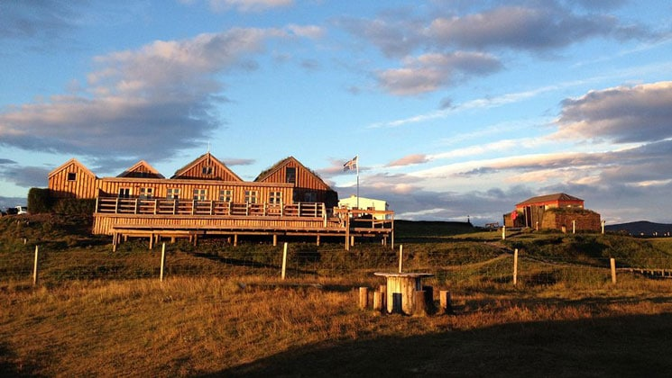 Long wooden building with sod roof, large deck & Iceland flag flying, on rolling grassland with farm equipment, at dusk.