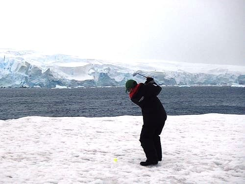 A man swings a golf club on Antarctica, celebrating having completed travel to every continent.