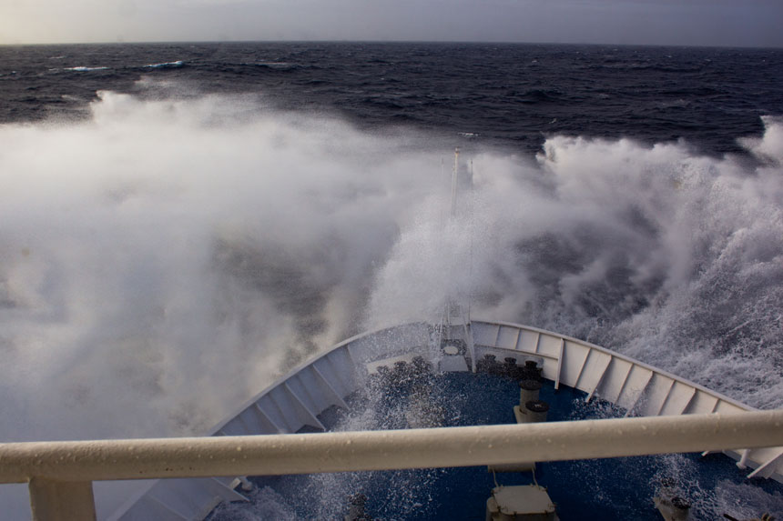 Bow of blue & white ship slams down into rough seas while crossing the Drake Passage, one of the places in Antarctica.