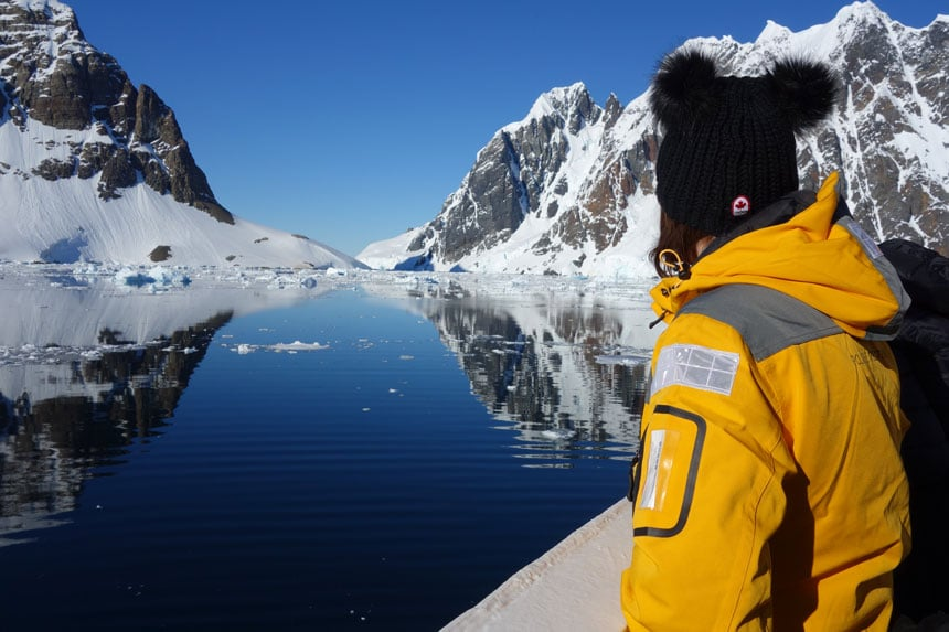 Woman in yellow jacket stands on ship bow looking at the Lemaire Channel a stretch of glassy water with snow-covered, rocky mountains on either side, on a sunny day in Antarctica.