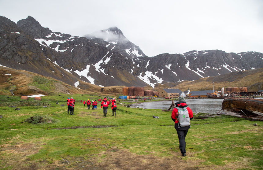 Travelers in red jackets walk toward rusted equipment, over bright green grass along the water in Grytviken, South Georgia, on a cloudy day with volcanic mountains beside.
