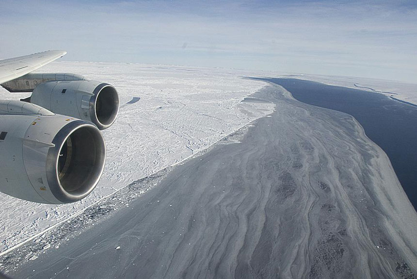 View out a plane window just behind the wing, looking down on the Larsen Ice Shelf, a place in Antarctica, with endless miles of snow tundra & a small inlet of water.