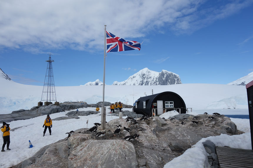 British flag flies outside a dark tube of a building with penguins on rocks in front & people in yellow jackets beside on a sunny day at Port Lockroy in Antarctica.
